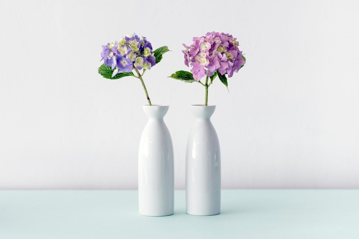 One vase with purple flowers and one vase with pink flowers